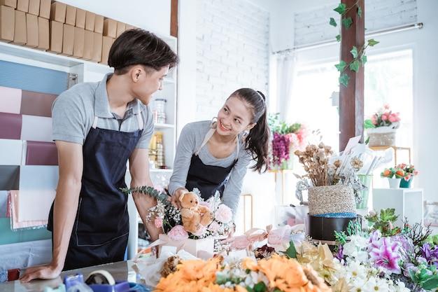 Heureux jeune homme et femme souriante parlant tout en travaillant ensemble dans un magasin de fleurs