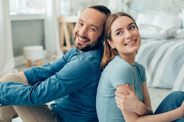 Heureux jeune homme et femme en vêtements décontractés bleus assis dans la chambre et profitant de la quarantaine ensemble