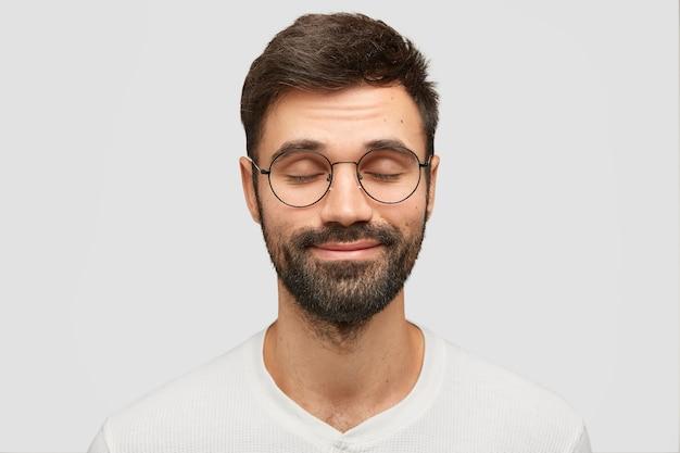 Heureux jeune homme ferme les yeux et imagine quelque chose d'agréable, rêve de choses incroyables