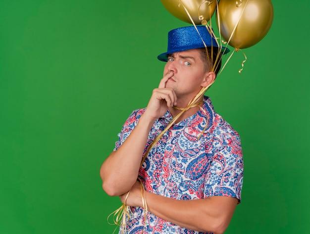 Heureux jeune homme de fête portant un chapeau bleu tenant des ballons attachés autour du cou mettant le doigt sur la joue isolé sur vert