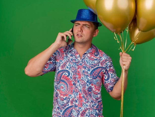 Heureux jeune homme de fête portant un chapeau bleu tenant des ballons et parle au téléphone isolé sur vert