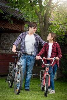 Heureux jeune homme et fille souriante posant avec des vélos au parc