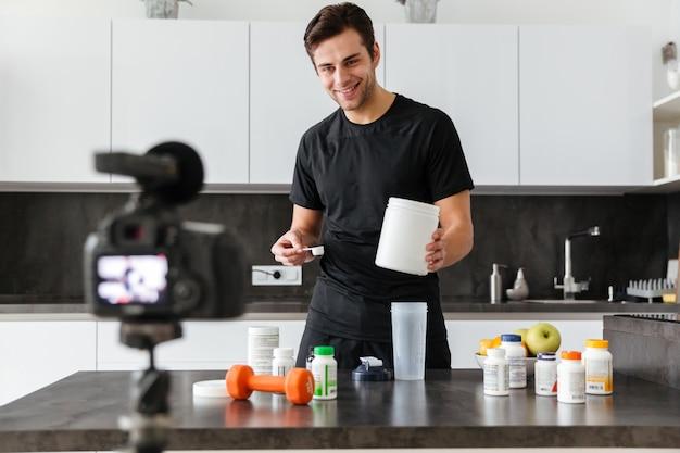Heureux jeune homme filmant son épisode de blog vidéo