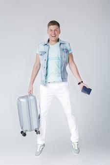 Heureux jeune homme en gilet en denim avec valise et saut de passeport