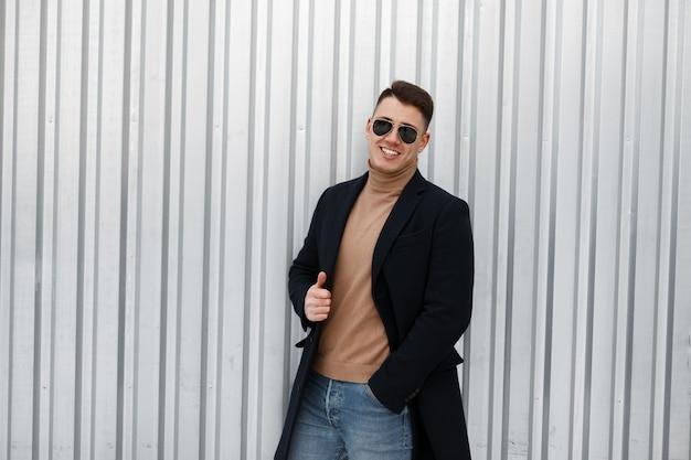 Heureux jeune homme hipster en manteau d'automne élégant en pull tricoté dans des lunettes de soleil à la mode en jeans bleu est debout et montrant les pouces vers le haut près du mur métallique