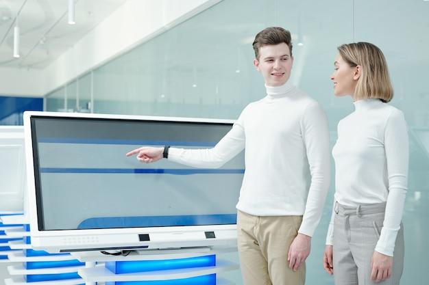 Heureux jeune homme intelligent regardant son collègue ou client tout en présentant un nouveau logiciel futuriste sur écran en laboratoire