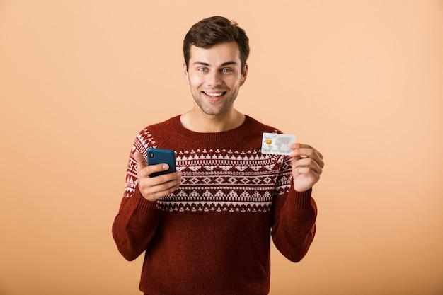 Heureux jeune homme isolé sur mur beige à l'aide de téléphone tenant une carte de crédit