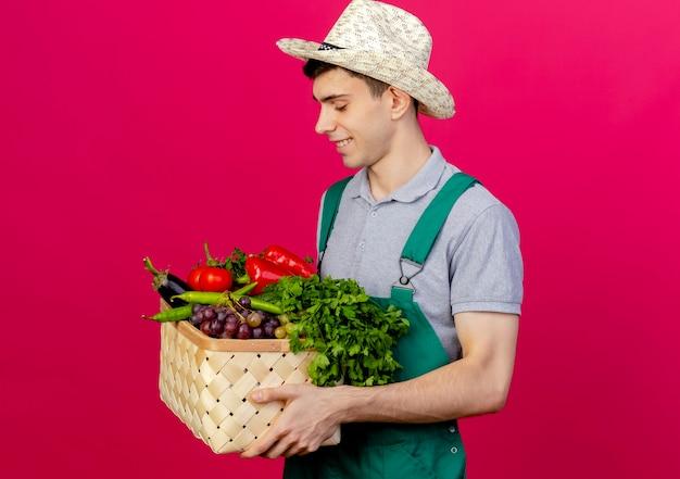 Heureux jeune homme jardinier portant chapeau de jardinage se tient sur le côté tenant et regardant le panier de légumes