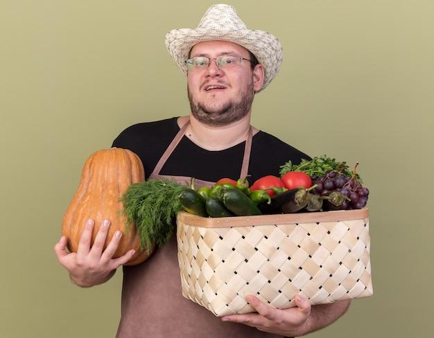 Heureux jeune homme jardinier portant chapeau de jardinage tenant un panier de légumes avec citrouille isolé sur mur vert olive