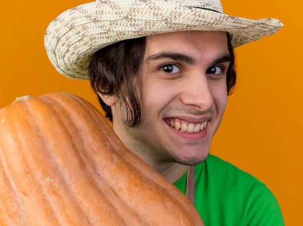 Heureux jeune homme jardinier en tablier et chapeau montrant la citrouille souriant largement avec un visage heureux debout sur fond orange
