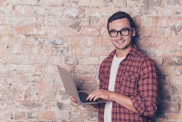 Heureux jeune homme à lunettes à l'aide d'un ordinateur portable moderne