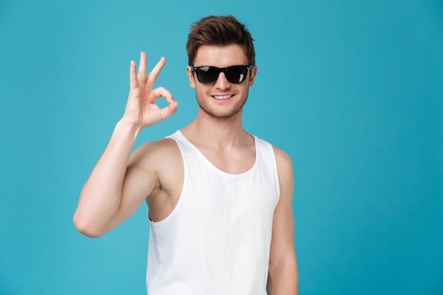 Heureux jeune homme à lunettes de soleil montrant un geste correct