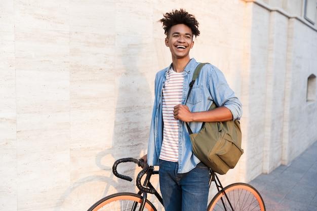 Heureux jeune homme marchant avec vélo à l'extérieur dans la rue