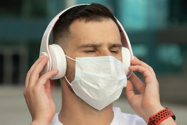 Heureux jeune homme en masque médical de protection écouter de la musique avec des écouteurs bluetooth sans fil. coronavirus covid-19.