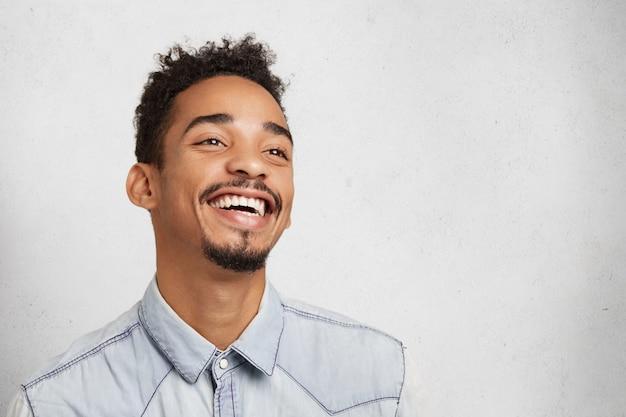 Heureux jeune homme métis positif avec moustache et barbe, sourit joyeusement