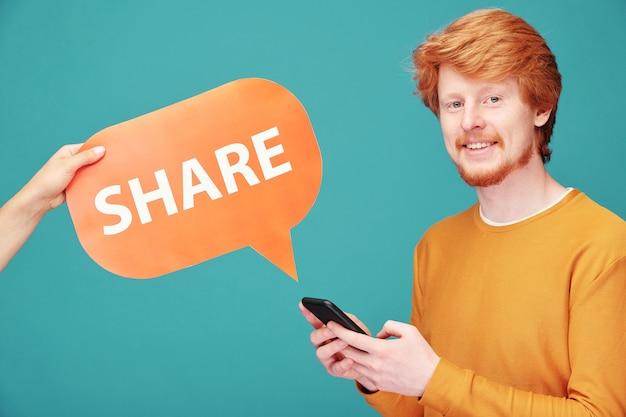Heureux jeune homme millénaire avec gadget mobile partageant sa photo ou vidéo dans les réseaux sociaux tout en faisant défiler dans le smartphone