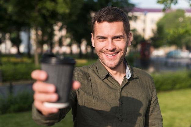 Heureux jeune homme montrant une tasse de café jetable au parc