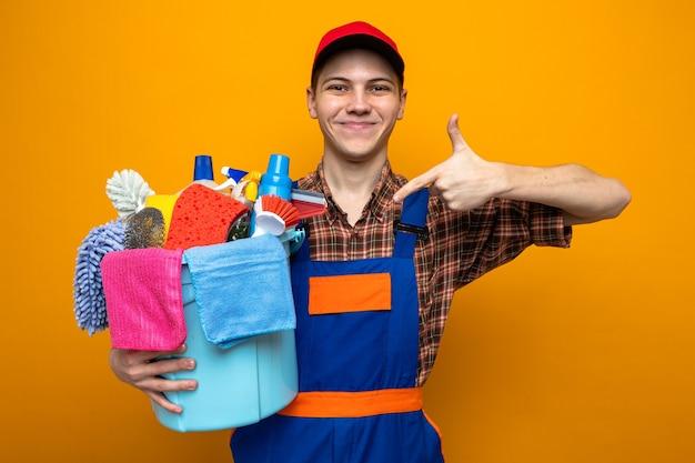 Heureux jeune homme de nettoyage portant un uniforme et une casquette tenant et pointant sur un seau d'outils de nettoyage