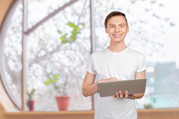 Heureux jeune homme avec ordinateur portable