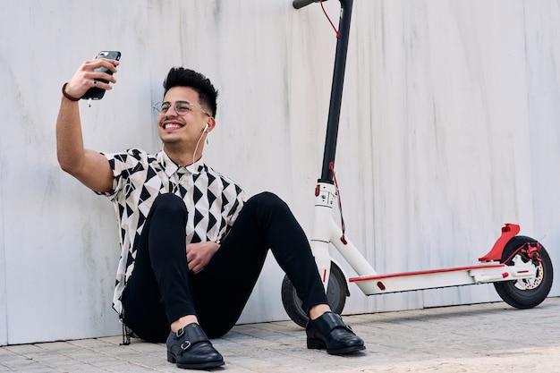Heureux jeune homme parlant au téléphone assis sur le sol