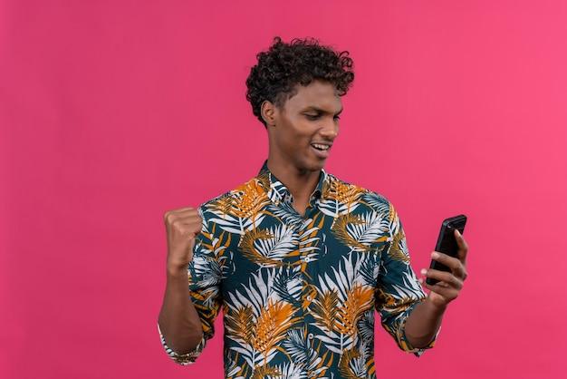 Heureux jeune homme à la peau foncée avec des cheveux bouclés en chemise imprimée de feuilles en regardant son smartphone avec le poing serré