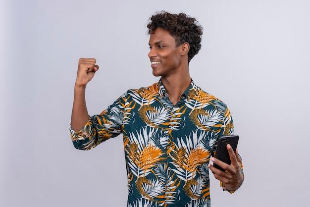 Heureux jeune homme à la peau foncée avec des cheveux bouclés en chemise imprimée de feuilles tenant un smartphone tout en regardant le poing serré