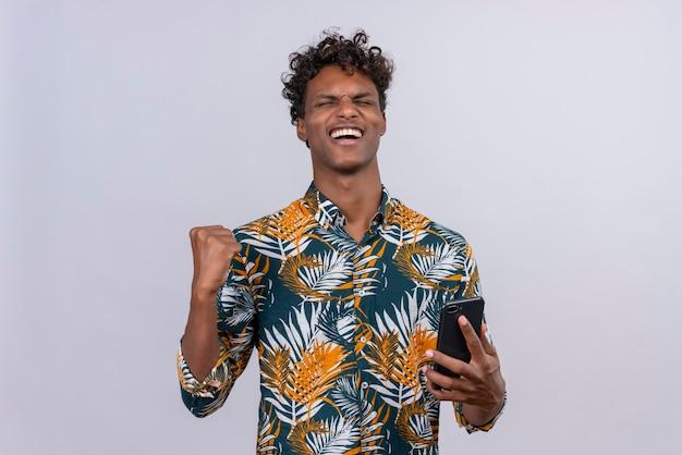 Heureux jeune homme à la peau sombre et aux cheveux bouclés en chemise imprimée de feuilles tenant son smartphone avec le poing serré