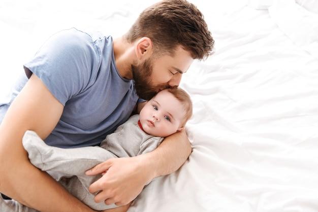 Heureux jeune homme père papa autre embrassant son petit enfant