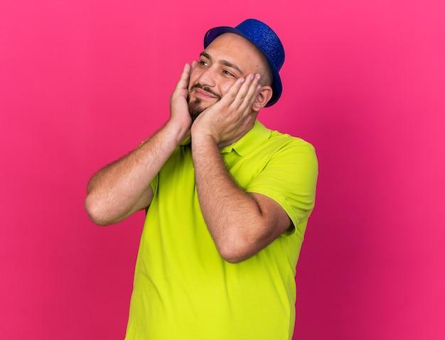 Heureux jeune homme portant un chapeau de fête mettant les mains sur les joues