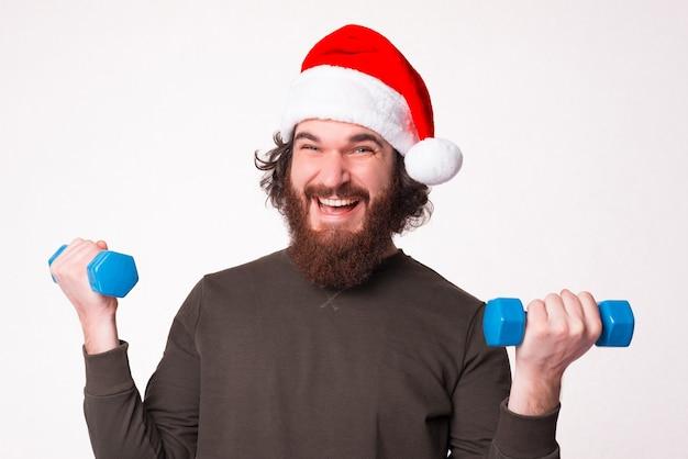 Heureux jeune homme, portant un chapeau de noël tient de petits haltères.
