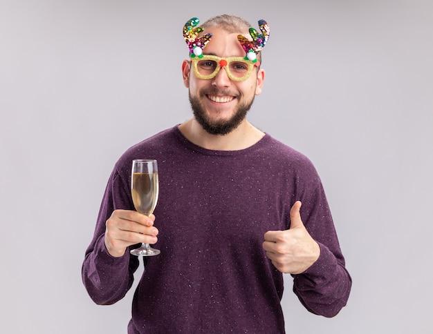 Heureux jeune homme en pull violet et lunettes drôles tenant un verre de champagne regardant la caméra avec le sourire sur le visage ferrant les pouces vers le haut debout sur fond blanc