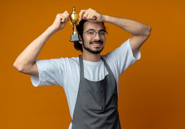 Heureux jeune homme de race blanche coiffeur portant des lunettes et bande de cheveux ondulés en uniforme soulevant la coupe du gagnant isolé sur fond orange