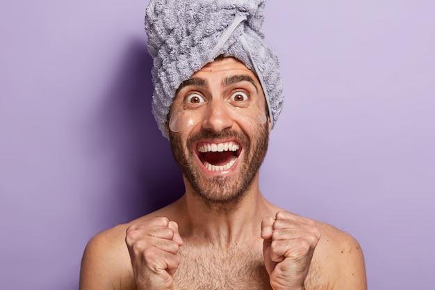 Heureux jeune homme de race blanche avec des coussinets de gel sous les yeux, pose torse nu, serviette sur la tête