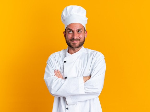 Heureux jeune homme de race blanche cuisinier en uniforme de chef et casquette debout avec une posture fermée en levant