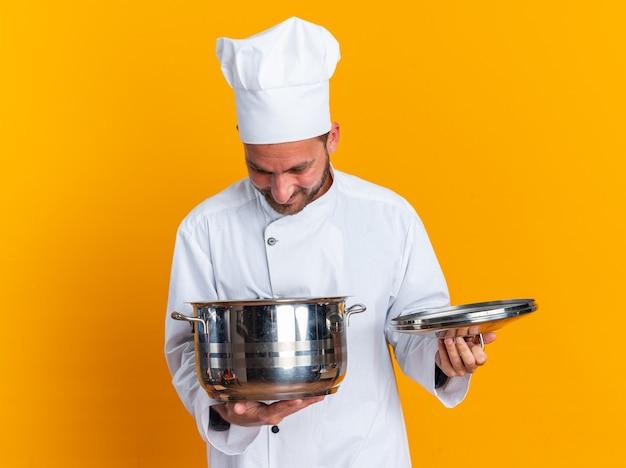 Heureux jeune homme de race blanche cuisinier en uniforme de chef et chapeau tenant le pot et le couvercle du pot regardant à l'intérieur du pot