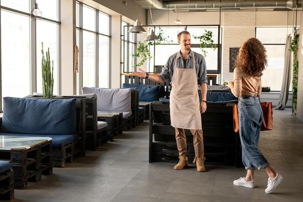 Heureux jeune homme regardant sa femme excitée se déplaçant vers lui tout en exprimant la joie d'ouvrir leur propre restaurant