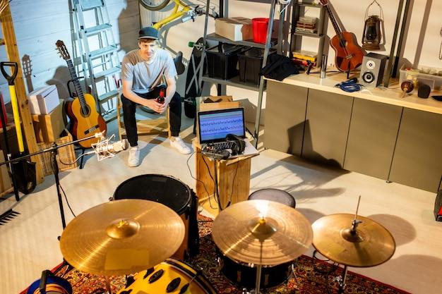 Heureux jeune homme reposant en tenue décontractée assis devant une batterie et d'autres trucs pour enregistrer de la musique dans un garage tout en buvant de la bière