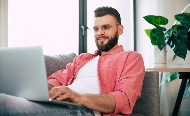 Heureux jeune homme séduisant barbu à lunettes et vêtements décontractés avec un ordinateur portable sur le canapé à la maison ou à l'appartement est relaxin ou travaille