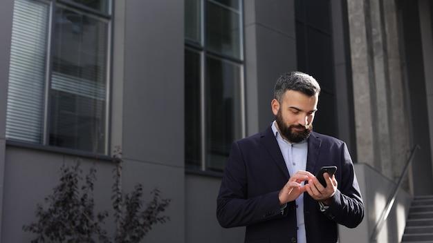 Heureux jeune homme souriant à l'aide d'applications de téléphonie mobile, sms, navigation sur internet, regarder des vidéos, tapoter, regarder smartphone
