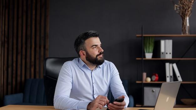Heureux jeune homme souriant à l'aide d'applications de téléphonie mobile, sms, navigation sur internet, regarder des vidéos, toucher.