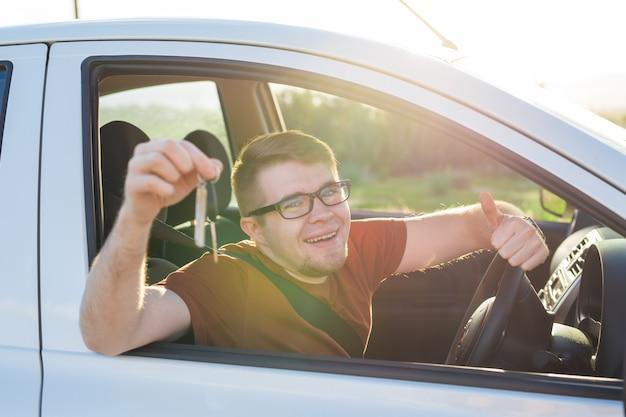 Heureux jeune homme souriant assis à l'intérieur d'une nouvelle voiture avec des clés.