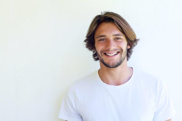 Heureux jeune homme souriant contre le mur blanc
