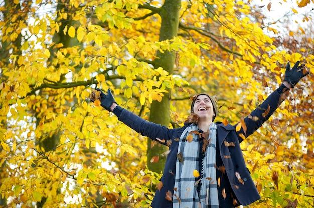 Heureux jeune homme souriant et jetant des feuilles à bras ouverts