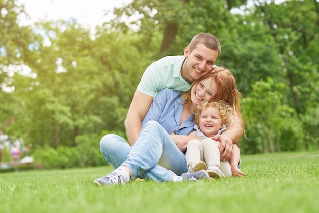 Heureux jeune homme souriant joyeusement embrassant sa belle femme et sa fille assise sur l'herbe ensemble copyspace famille amour émotions week-end plaisir affection parents mariage.