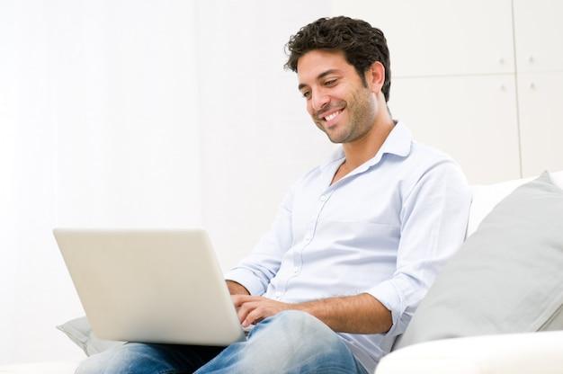 Heureux jeune homme souriant regardant et travaillant sur ordinateur portable à la maison
