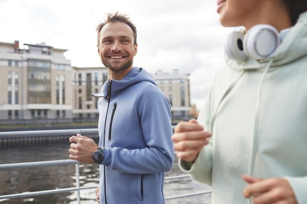 Heureux jeune homme souriant à sa petite amie pendant qu'ils font du jogging ensemble dans la ville
