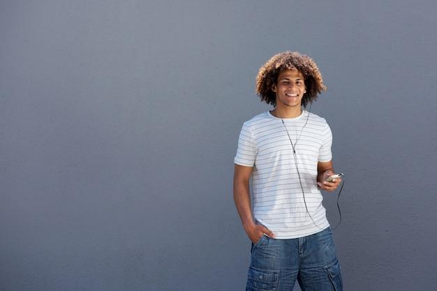 Heureux jeune homme souriant avec un téléphone intelligent et des écouteurs