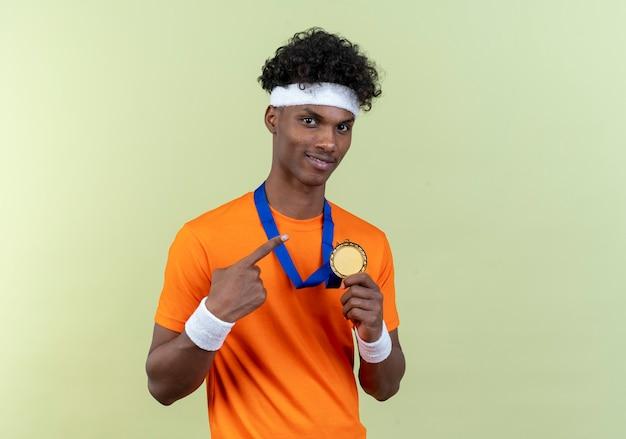 Heureux jeune homme sportif afro-américain portant un bandeau et un bracelet tenant et pointe la médaille sur le cou