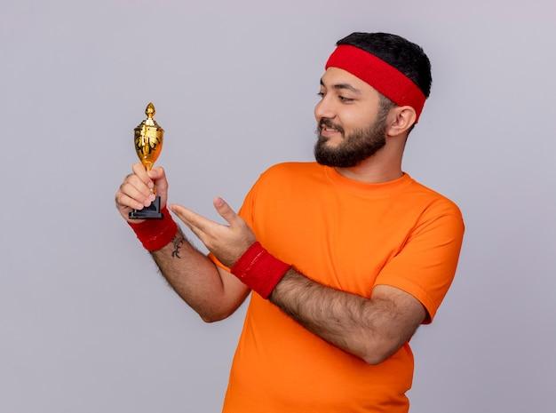 Heureux jeune homme sportif portant bandeau et bracelet tenant et points avec la main à la coupe gagnant isolé sur fond blanc