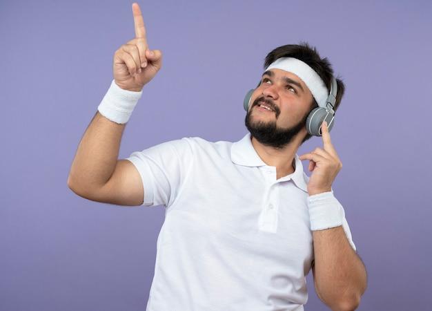 Heureux jeune homme sportif à la recherche de porter un bandeau et un bracelet avec des points d'écouteurs vers le haut